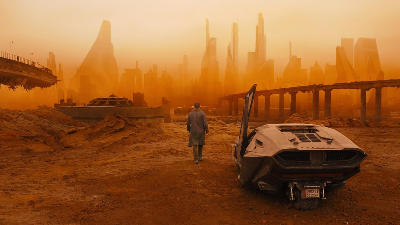 "Blade Runner ""K"" walks toward a desolate cityscape."